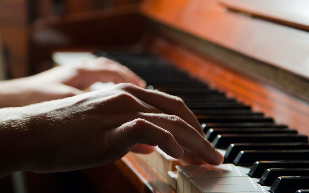 Close up hands of person playing an upright piano at home